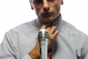 Distressed looking man at a microphone